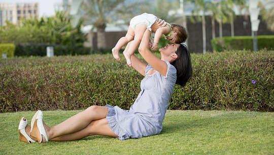 lächelnde Mutter, die im Gras sitzt und ein Kind hochhält