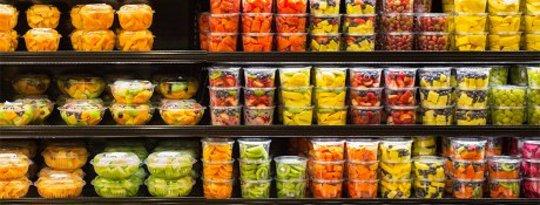 Surtido de frutas cortadas en envases de plástico en exhibición para la venta en el supermercado
