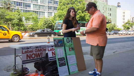 A woman from New York Public Interest Research Group speaks to a passerby about the potential dangers of GMOs in front of a Whole Foods Market in New York on June 3, 2014. (Jonathan Zhou/Epoch Times)