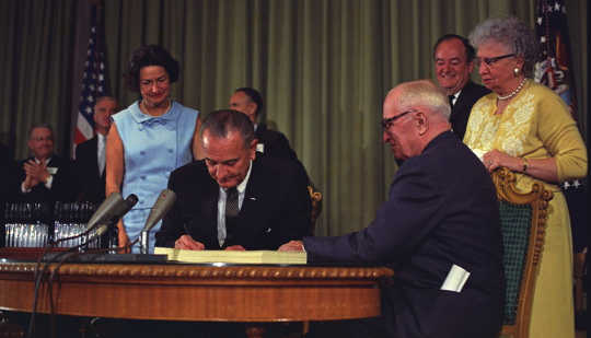 President Lyndon B. Johnson signs the Medicare Bill. President Harry S. Truman is seated next to him. LBJ Library
