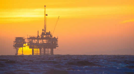 The sun sets on an offshore oil rig. Image: troy_williams via Flickr