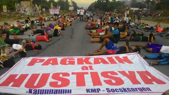 Bønder blokkerer en nasjonal motorvei i Koronadal City, Filippinene. Den store banneret lyder: Mat og rettferdighet. Bilde av Kath Cortez. Kilde: Facebook