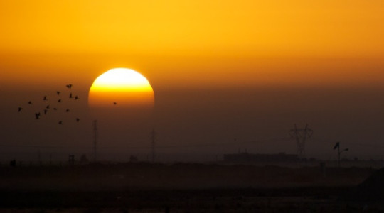 The rising sun is partially obscured by a dawn dust storm in Iraq. Image: Elliott Plack via Flickr