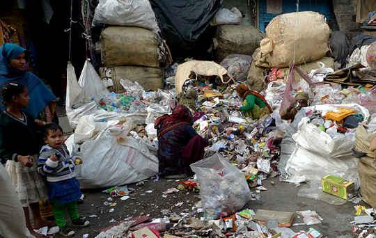 Một phụ nữ Ấn Độ sắp xếp các vật liệu có thể tái sử dụng và tái chế từ rác được thu gom ở phía đông bắc Delhi.