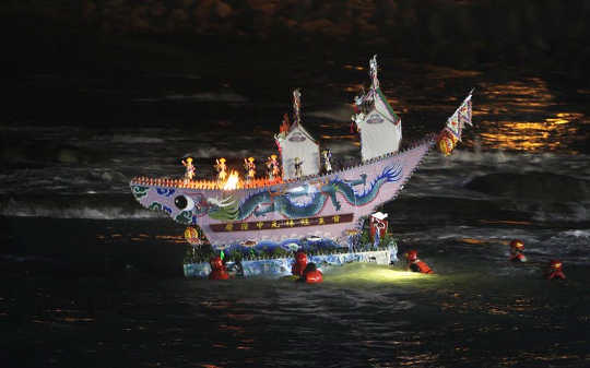 An elaborate model house is being guided into the ocean as an offering to wandering ghosts during the beginning of the Ghost Month Festival in Taiwan.