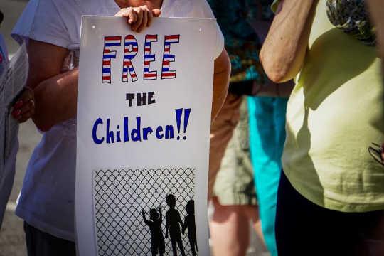Am Juni 14, 2018: Ein Demonstrant bei einer Zusammenkunft von Keep Families Together in Detroit, Michigan (welche Schäden verursachen wir unseren Kindern und uns selbst?)