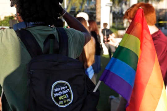 Tässä 31-kuvassa 2018-kuva, jossa on sateenkaarilippu, kuuntelee puhujia äänestyksessä elämässämme rallissa Keski-Floridan yliopistossa Orlandossa, Fla.