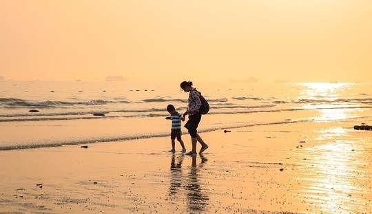 barn och vuxen som går hand i hand på en strand