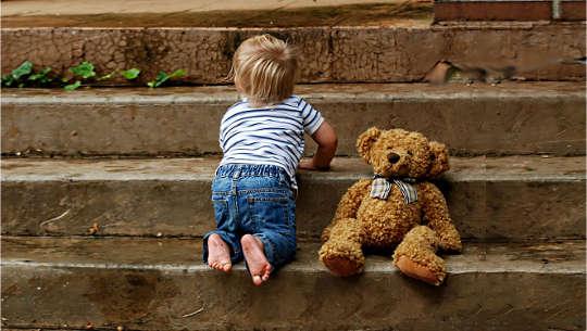 παιδί που σέρνεται μερικά σκαλιά με το αρκουδάκι του
