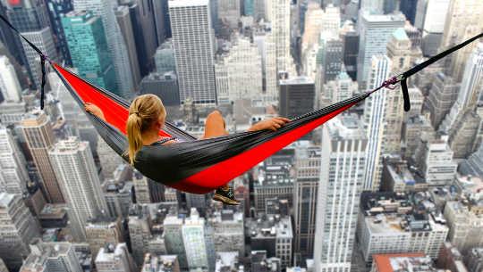 κορίτσι σε μια αιώρα που κρέμεται πάνω από τον ορίζοντα των ουρανοξυστών της μεγάλης πόλης