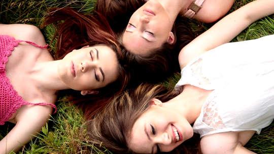 tiga wanita muda, tersenyum, berbaring telentang di luar