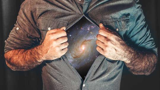 bărbat care își ține cămașa deschisă pentru a arăta galaxia și universul (ca un simbol Superman)