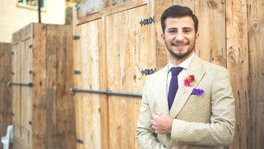 junger weißer Mann, der einen Anzug trägt, der vor verschlossenen Türen steht