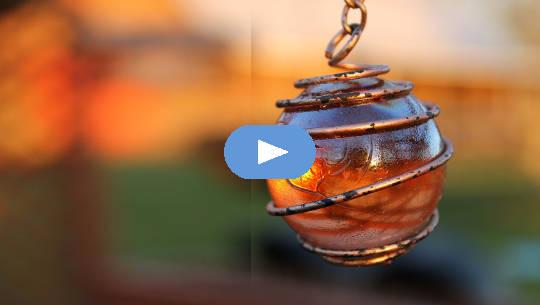 uma esfera brilhante em um pingente com um envoltório de fio de cobre