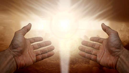 duas mãos abertas para uma luz radiante
