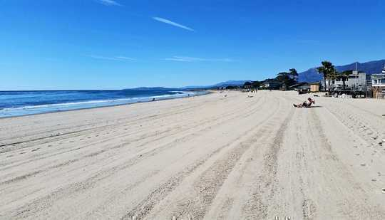 The image shows Carpinteria City Beach, with flat, groomed sands and blue sky.
