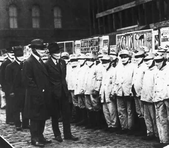 Officials wearing gauze masks inspect Chicago street cleaners for the flu, 1918