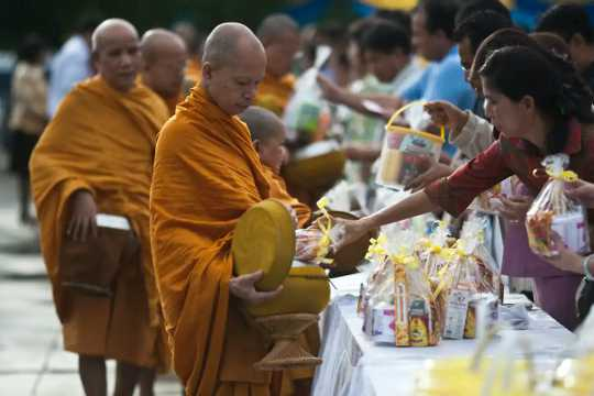 Thai Buddhist monks accepting food donations