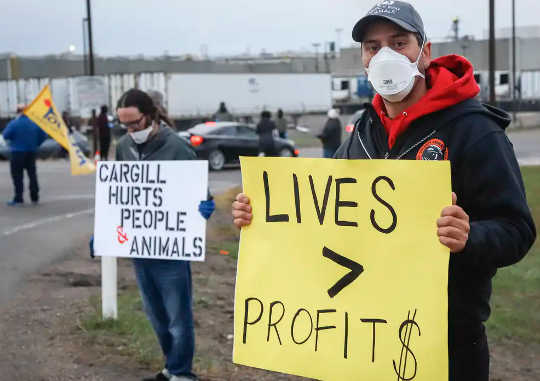Penunjuk perasaan berdiri di tepi jalan ketika pekerja kembali ke kilang memproses daging lembu Cargill di High River, Alta.,