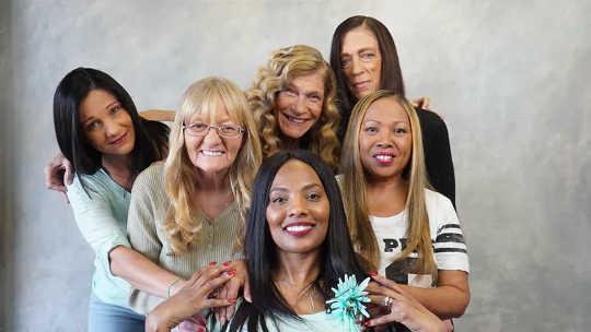 Overlevende van huiselijk geweld Vanessa Howard, front, wordt omringd door vrouwen die ze heeft geholpen door haar- en schoonheidsmake-overs te geven in Tampa, Florida. (hoe familie en vrienden kunnen helpen om huiselijk geweld te beëindigen)