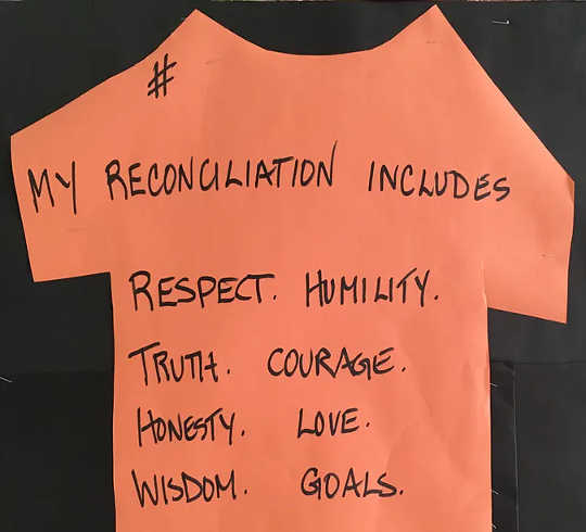 A handmade paper orange T-shirt reads: 'My reconciliation includes respect, humility, truth, courage, honesty, love, wisdom, goals. (how racism leads to poor attendance in schools)