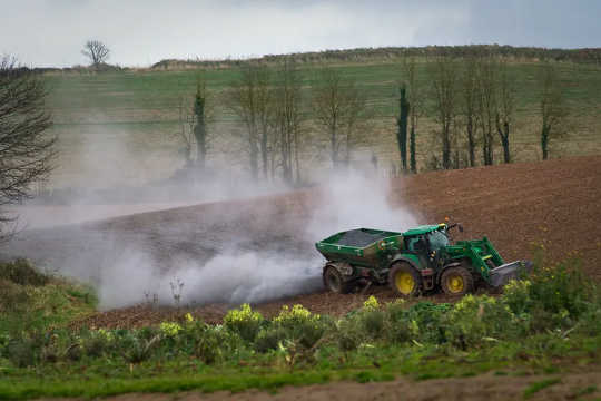 Spreading lime on a field in Devon, England to improve soil quality.