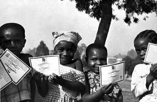 카메룬의 어린이들은 1975 년 천연두 예방 접종 증명서를 자랑합니다.