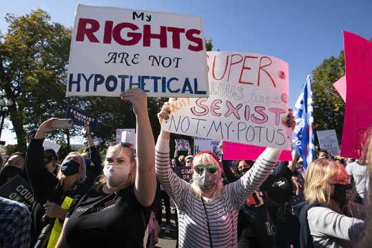 Para pengunjuk rasa memegang plakat di depan Mahkamah Agung di Washington, DC (apa arti kemenangan atau kekalahan truf bagi feminisme)
