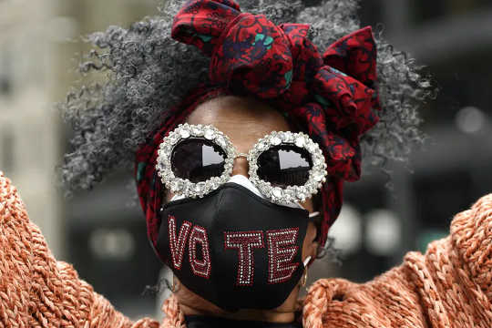 Jackie Simmons mengenakan topeng dengan pesan saat dia menghadiri Pawai Wanita di pusat kota Chicago pada 17 Oktober 2020. Lusinan aksi Pawai Wanita direncanakan dari New York ke San Francisco untuk menandakan penentangan terhadap Presiden Donald Trump dan kebijakannya.
