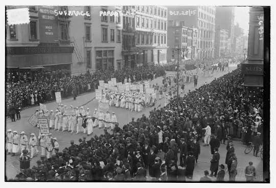 Tijdens optochten stonden de witte kledingstukken van de demonstranten in schril contrast met de toeschouwers langs de stoep.