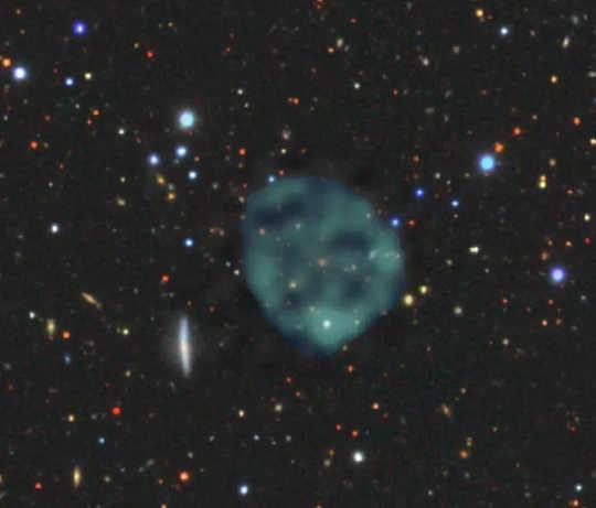 Den spøkelsesaktige ORC1 (blå / grønn fuzz), på bakgrunn av galaksene ved optiske bølgelengder.