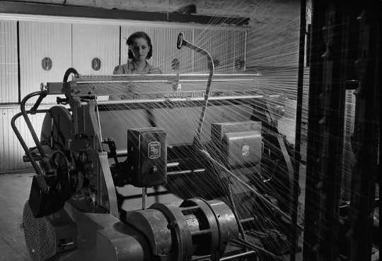Een arbeider bedient een warper bij Montreal Cottons Ltd. in Valleyfield, Qué.