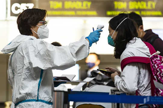 Los viajeros son examinados y se les revisa la temperatura en el Aeropuerto Internacional de Los Ángeles.
