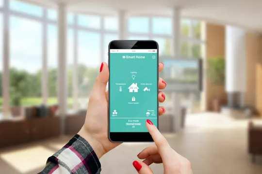 Người phụ nữ sử dụng ứng dụng smarthome trên điện thoại của mình.