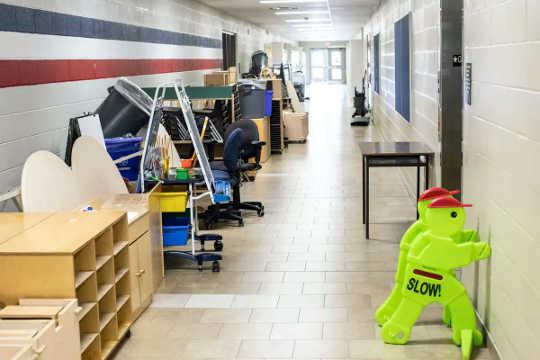 Escritorios, sillas y estanterías se empujan contra la pared de un pasillo vacío en una escuela.