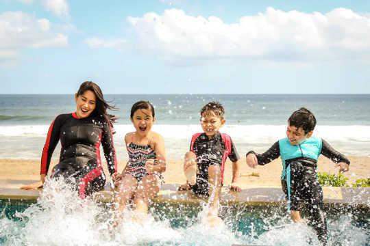 الأسرة تتدفق في الماء على شاطئ البحر.