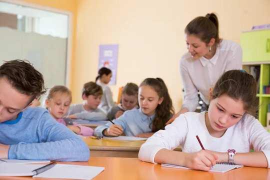 учитель смотрит на учеников, работающих в классе
