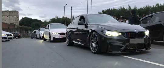 BMW et autres véhicules garés dans le parking.