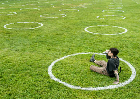 Ein Mann sitzt in einem mit Kreide gezeichneten Kreis in einem Park und nippt an einem Bier.