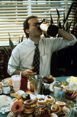 Phil trinkt Kaffee direkt aus dem Krug über einem mit Donuts gefüllten Tisch.