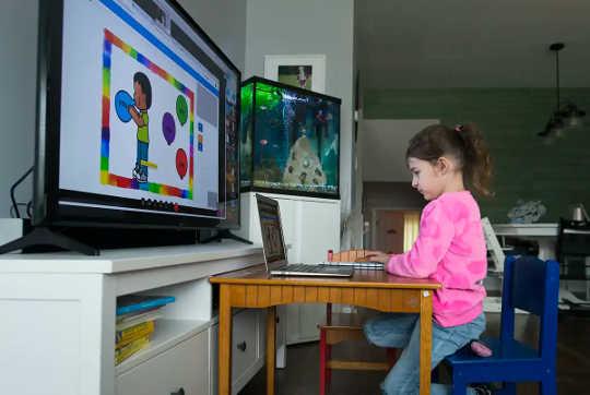 Ang isang batang babae sa isang rosas na sweatshirt ay nakaupo sa harap ng isang laptop at isang mas malaking monitor ng computer na nagpapakita ng mga aralin.