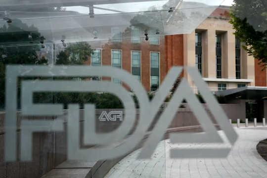 Uma visão de um painel de vidro com o logotipo da FDA e o prédio da FDA ao fundo