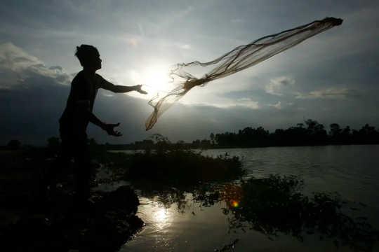 Un homme jette un filet de pêche dans un plan d'eau avec le soleil qui se lève en arrière-plan.