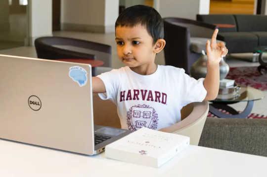 Seorang anak laki-laki dengan kaos Harvard memeriksa laptop dengan satu jari teracung.