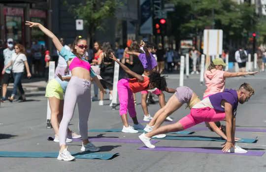 Menschen in Lycra, einige davon in Pink, machen Yoga und strecken sich auf Asphalt.