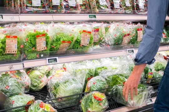Le bras d'une personne cherche un paquet de légumes verts à partir d'une sélection de légumes verts et de laitues dans une épicerie.