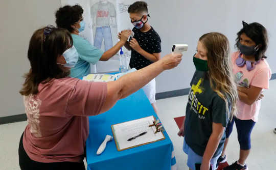 Hai giáo viên đeo khẩu trang kiểm tra học sinh phát sốt bằng súng nhiệt độ