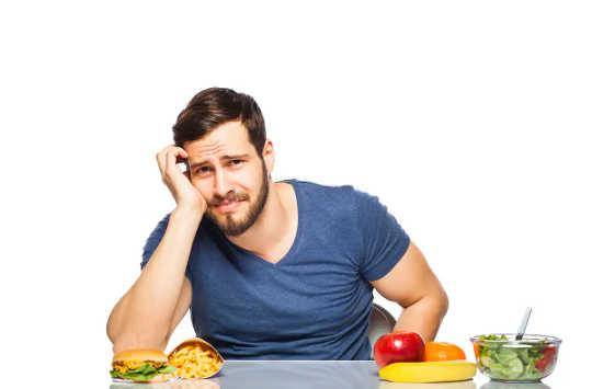 مرد تصمیم می گیرد بین غذای سالم و ناسالم.