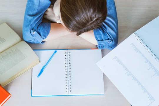Una estudiante descansa su cabeza, durmiendo en una mesa, con libros abiertos frente a ella.
