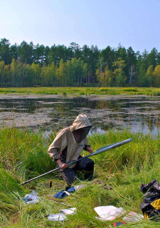 Forsker i beskyttelsesklær satt ved innsjøen i torvmyr